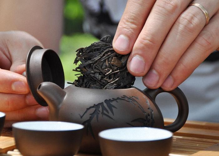 Насыпать в чайник несколько ложек черного чая