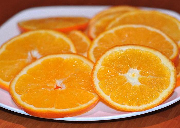 Положить в бокал несколько долек апельсина