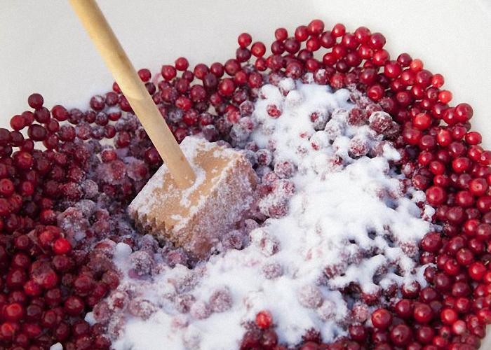 Клюкву насыпать в миску и добавить сахар