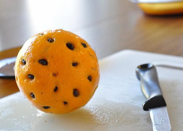 Сделать надрезы по окружности апельсина и вставить кофейные зерна